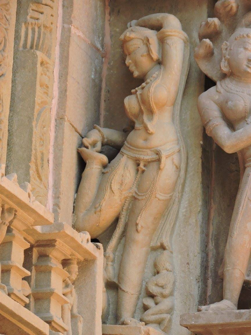 Statue of a lady taking out thorns from her legs in Khajuraho