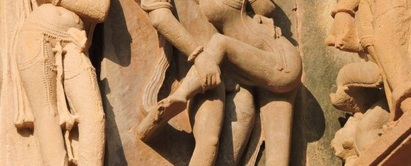 Statue of a woman hugging a man like vines around a tree in Khajuraho