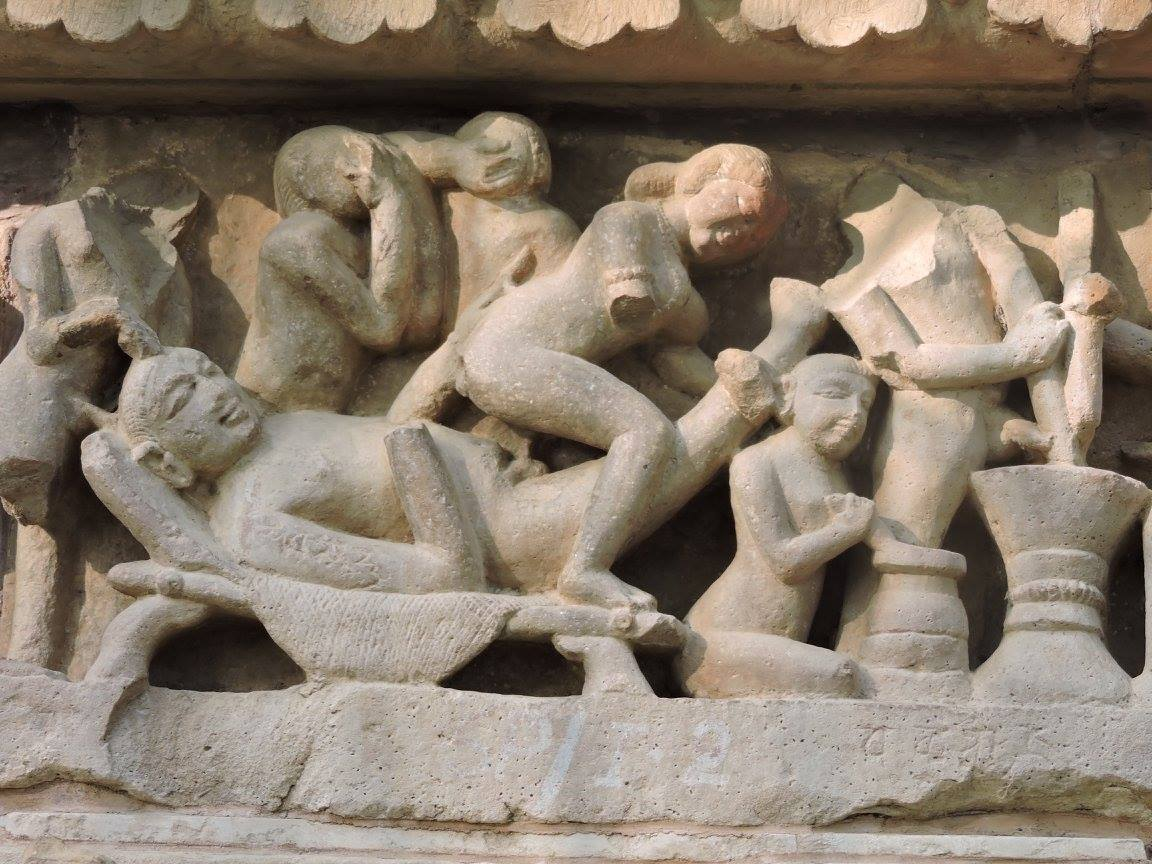 Statue of group love making in Khajuraho while two are making medicines to last long while two are shying away