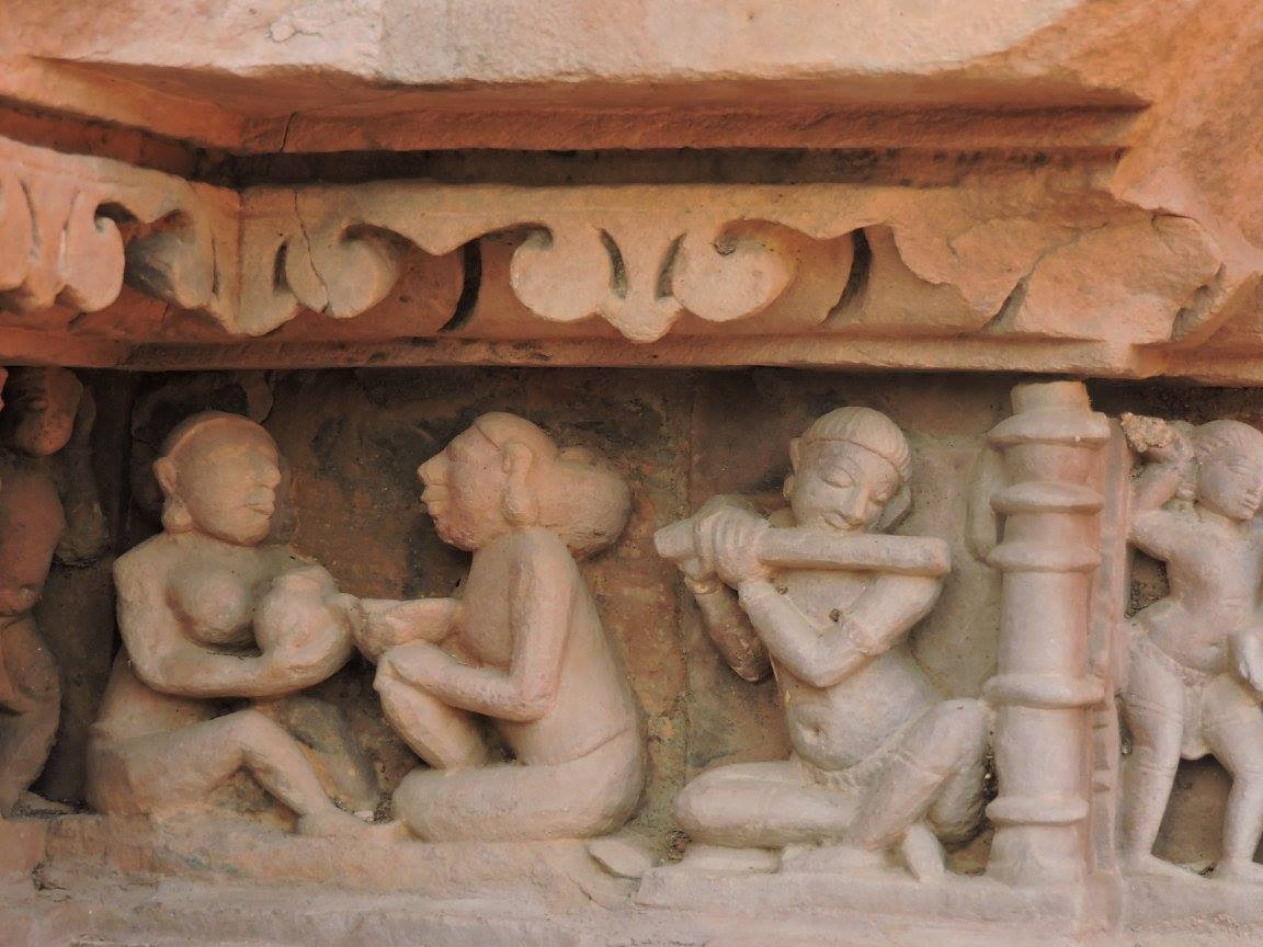 Statue of people drinking and playing music in Khajuraho
